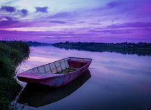 Romantic Time on Lake. Old Boat on calm lake shore Royalty Free Stock Image