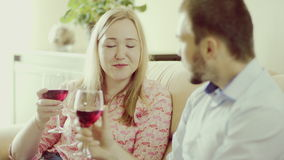 Romantic time together. Man and woman clinking glasses, drinking red wine and talking sitting at home stock video