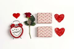 Romantic top down composition of the alarm clock, rose, gifts and hearts on white background. St. Valentines Day concept stock image