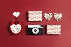 Romantic top down composition of the alarm clock, vintage camera, gifts and hearts on red background. St. Valentines Day concept stock photo