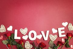 Romantic top down composition with the word love, rose, hearts and copy space on red background. St. Valentines Day concept stock images