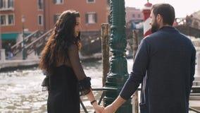 Romantic couple in Venice, Italy. Romantic tourist couple in love on pier in Venice, Italy. Back view. Beautiful view on bridge venetian gondolas boats on sea stock footage