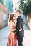 Romantic couple in Venice. Young pretty woman in rose dress and handsome man in black clothes hugging. Italy, Europe. Romantic travel couple in Venice on stock images