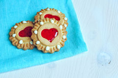 Romantic treat - butter shortbread cookies stuffed with red heart shaped jelly on the bright turquoise linen tablecloth. Some butter shortbread cookies stuffed Stock Image