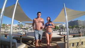 Romantic trip, cheerful male with girlfriend in swimsuits holding hands running on jetty at summer holidays. By sea stock video footage