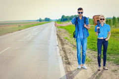 Romantic trip. Hitchhiking couple. Romantic young people standing on a highway and catching a passing car Royalty Free Stock Photography