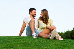 Romantic trip. Lovers sit on the grass. Royalty Free Stock Image