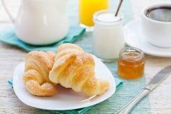 Romantic tropical breakfast Croissants, coffee, juice, honey and yogurt Royalty Free Stock Images