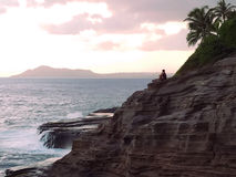Romantic Twilight. A romantic couple is enjoying a sunset and twilight of the west coast of Oahu island. Pacific waves are crashing into Hawaii island's royalty free stock image