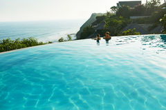 Romantic Vacation For Couple In Love. People In Summer Pool. Romantic Vacation For Couple In Love. Happy People Relaxing In Infinity Edge Swimming Pool Water Royalty Free Stock Photography