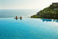 Romantic Vacation For Couple In Love. People In Summer Pool. Romantic Vacation For Couple In Love. Happy People Relaxing In Infinity Edge Swimming Pool Water Stock Photo