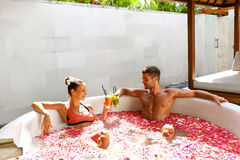 Romantic Vacation. Couple In Love Relaxing At Spa With Cocktails. Romantic Vacation. Couple In Love Relaxing, Bathing In Outdoor Flower Bath At Luxury Day Spa Royalty Free Stock Photo