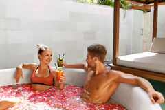 Romantic Vacation. Couple In Love Relaxing At Spa With Cocktails. Romantic Vacation. Couple In Love Relaxing, Bathing In Outdoor Flower Bath At Luxury Day Spa Stock Image