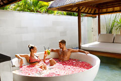 Romantic Vacation. Couple In Love Relaxing At Spa With Cocktails. Romantic Vacation. Couple In Love Relaxing, Bathing In Outdoor Flower Bath At Luxury Day Spa Royalty Free Stock Photos