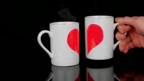 Romantic Valentine day. Cups of the hot tea with halves of the heart brings together to make a full heart. Romantic Valentine day. Cups of the hot tea painted stock video