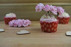 Some Valentines day romantic cup cakes with pink paper roses for decoration on top. A romantic valentine day food of strawberry and cream flavor cupcakes. With stock photography