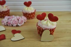 Some Valentines day romantic cup cakes with red love heart decorations on top and pink paper roses. A romantic valentine day food of strawberry and cream flavor royalty free stock photo