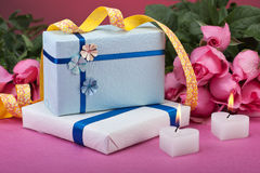 Romantic valentine gifts. Wrapped valentine presents with candles and roses Stock Image