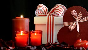 Romantic Valentine gifts, zoom. Romantic Valentine gifts with burning candles on black background, zoom in and out stock video