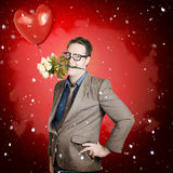 Romantic valentine man holding flowers on date. Quirky valentine portrait of a happy romantic man holding flowers in mouth with red love heart balloon. Gift of Royalty Free Stock Photos