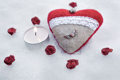 Romantic Valentine Plush Heart With A Winged Metal Heart On Ice Besides A Peaceful Tea Light Surrounded By Rose Bloom Royalty Free Stock Photos