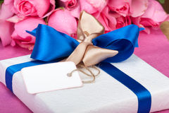 Romantic valentine present with note. And roses in background Stock Image