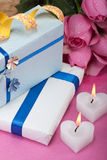 Romantic valentine presents. Two wrapped presents with heart-shaped candles and roses Stock Photos