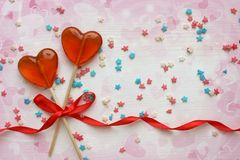 Romantic Valentine`s day background. Lollipops in the shape of heart close up on white background. Copy space.The concept of Valentine`s day. Pink bokeh, stars royalty free stock images