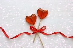 Romantic Valentine`s day background. Lollipops in the shape of heart close up on white background. Copy space.The concept of Valentine`s day. Pink bokeh, stars royalty free stock image