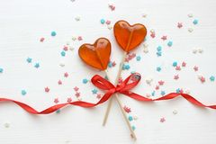 Romantic Valentine`s day background. Lollipops in the shape of heart close up on white background. Copy space.The concept of Valentine`s day. Pink bokeh, stars stock photography