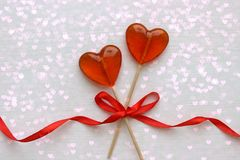 Romantic Valentine`s day background. Lollipops in the shape of heart close up on white background. Copy space.The concept of Valentine`s day. Pink bokeh, stars stock photos