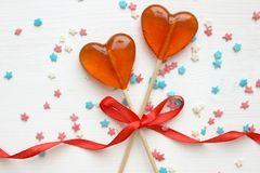 Romantic Valentine`s day background. Lollipops in the shape of heart close up on white background. Copy space.The concept of Valentine`s day. Pink bokeh, stars stock images