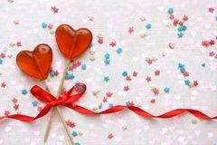 Romantic Valentine`s day background. Lollipops in the shape of heart close up on white background. Copy space.The concept of Valentine`s day. Pink bokeh, stars royalty free stock photography