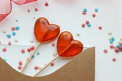 Romantic Valentine`s day background. Valentine`s day gift. Postcard and two lollipops in the shape of red hearts. stock photos
