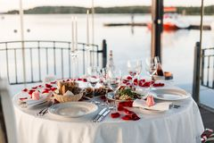 Romantic Valentine`s Day dinner setup with rose petals. Romantic Valentine`s Day dinner, red decoration with rose petals, violin and wineglasses in a restaurant royalty free stock image