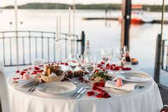 Romantic Valentine`s Day dinner setup with rose petals royalty free stock photo