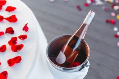 Romantic Valentine`s Day dinner setup with rose petals. Romantic Valentine`s Day dinner, red decoration with rose petals, violin and wineglasses in a restaurant stock photo