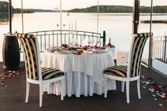 Romantic Valentine`s Day dinner setup with rose petals royalty free stock images