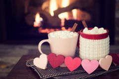 Romantic Valentine`s Day Fireplace Scene with Red and Pink Cocoa Mugs and Wood Hearts Garland in Cozy Setting with room or space f. Or copy, text, or your words stock images