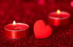 Romantic Valentine`s Day. Lit scented candles and red heart on bright sparkling background with bokeh effect. Romantic Valentine`s Day. Lit scented candles and royalty free stock photos