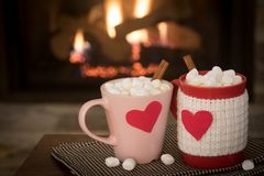 Romantic Valentine`s Day, Warm Fireplace Scene with Red and Pink Cocoa Mugs with red Hearts in Cozy Living room. With space for copy, text, or your words or Stock Photography