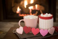 Romantic Valentine`s Day, Warm Fireplace Scene with Red and Pink Cocoa Mugs and Wood Hearts Garland in Cozy Living room with space Stock Photos