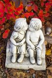 Romantic, valentine statue with two kissing children. Valentine love, kissing statue and red leaves stock photography