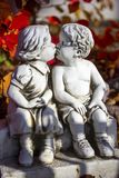 Romantic, valentine statue with two kissing children. Valentine love, kissing statue and red leaves royalty free stock photos
