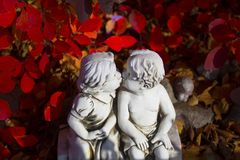 Romantic, valentine statue with two kissing children. Valentine love, kissing statue and red leaves royalty free stock photo