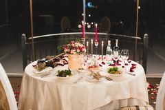 Romantic table setting with wine, beautiful flowers in box, empty glasses, rose petals and candles royalty free stock photo
