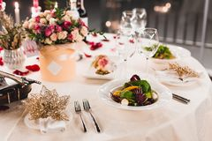 Romantic table setting with wine, beautiful flowers in box, empty glasses, rose petals and candles royalty free stock photos