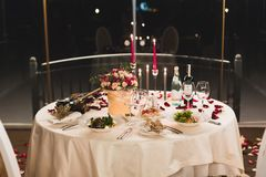 Romantic table setting with wine, beautiful flowers in box, empty glasses, rose petals and candles stock images