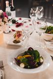 Romantic table setting with wine, beautiful flowers in box, empty glasses, rose petals and candles royalty free stock photography