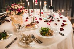 Romantic table setting with wine, beautiful flowers in box, empty glasses, rose petals and candles stock photography
